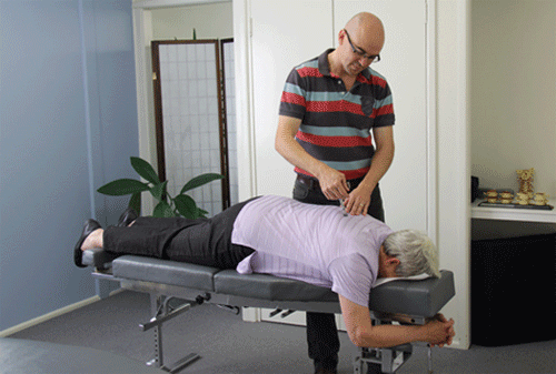 Our Chiropractor Dr David Malone using the Activator to adjust a client